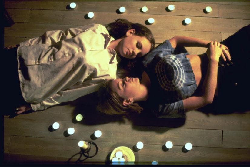 Zwei Frauen liegen mit geschlossenen Augen am Boden umringt von Kerzen.